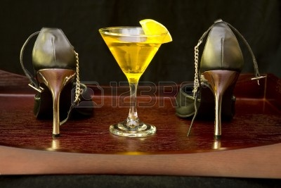 3387538-pair-of-black-high-heel-shoes-and-yellow-cocktail-on-a-wooden-tray